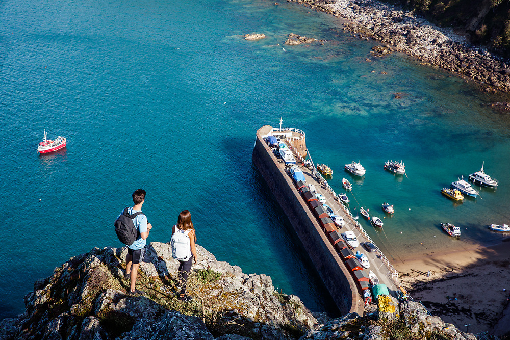 Adventurous couple exploring the cliff paths and looking out over the cliff edge towards Bonne Nuit harbour and beach below with boats up in crystal clear water in Jersey, Channel Islands