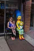 "Real-life mother and child with Marge and Maggie Simpson characters in Manhattan, New York City. Sitting next to the fictional mother, the real-life mom poses for a family photo in a scene of maternity and motherhood. Marjorie Jacqueline ""Marge"" Simpson (née Bouvier), is the beautiful happy homemaker and full-time mom of the Simpson family. With her husband Homer, she has three (later four) children: Bart, Hugo, Lisa, and Maggie."