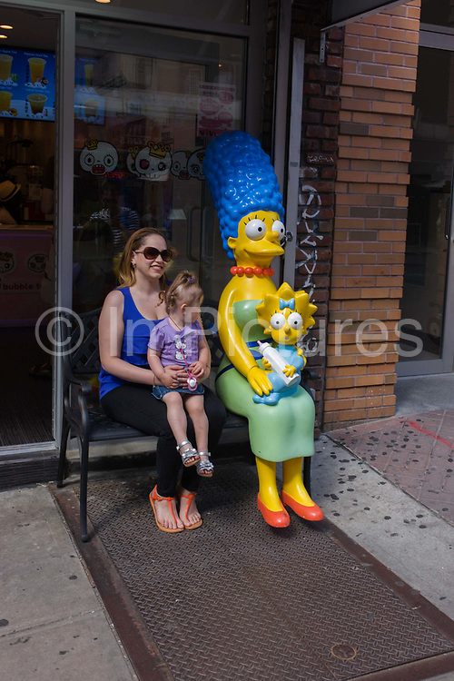 """Real-life mother and child with Marge and Maggie Simpson characters in Manhattan, New York City. Sitting next to the fictional mother, the real-life mom poses for a family photo in a scene of maternity and motherhood. Marjorie Jacqueline """"Marge"""" Simpson (née Bouvier), is the beautiful happy homemaker and full-time mom of the Simpson family. With her husband Homer, she has three (later four) children: Bart, Hugo, Lisa, and Maggie."""