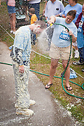 A participant in the Grits Roll is hosed down after wallowing in a pool of grits during the annual World Grits Festival in St George, SC