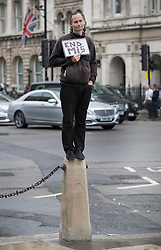 © Licensed to London News Pictures. 01/08/2016. London, UK.  A lone protestor stands on top of a bollard in Parliament Square holding a sign that reads 'END MI5' referring to the United Kingdom's domestic secret intelligence agency. Photo credit: Peter Macdiarmid/LNP