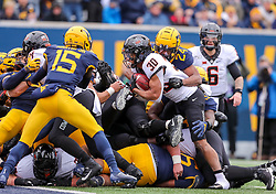 Nov 23, 2019; Morgantown, WV, USA; Oklahoma State Cowboys running back Chuba Hubbard (30) runs the ball and is tackled at the goal line by West Virginia Mountaineers cornerback Hakeem Bailey (24) during the first quarter at Mountaineer Field at Milan Puskar Stadium. Mandatory Credit: Ben Queen-USA TODAY Sports