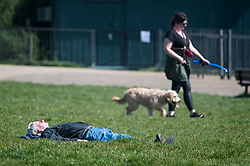 © Licensed to London News Pictures. 07/04/2020. London, UK. A man sunbathing at Hampstead Heath in London, during a pandemic outbreak of the Coronavirus COVID-19 disease. The public have been told they can only leave their homes when absolutely essential, in an attempt to fight the spread of coronavirus COVID-19 disease. Photo credit: Ben Cawthra/LNP