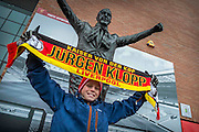 """13/12/2015<br /> Anfield Stadium, Liverpool<br /> <br /> Tore Digerues from Norway holds his Klopp scarve aloft in front of the Bill Shankly statue outside the """"Kop"""" end at Liverpool FC.<br /> <br /> German coach Jurgen Klopp took over as boss at Liverpool in October 2015. The stallholders outside the ground were not slow to spot a good sales opportunity and updated their merchandise with Klopp scarves, badges and tee shirts.<br /> ©Brian Hickey/Exclusivepix Media"""
