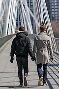 A gay couple walks hand-in-hand through nearly empty Golden Jubilee Bridge in London on Wednesday, March 25, 2020. After a vote of the British lawmakers to shut down Parliament for 4 weeks, due to the coronavirus outbreak. (Photo/Vudi Xhymshiti)
