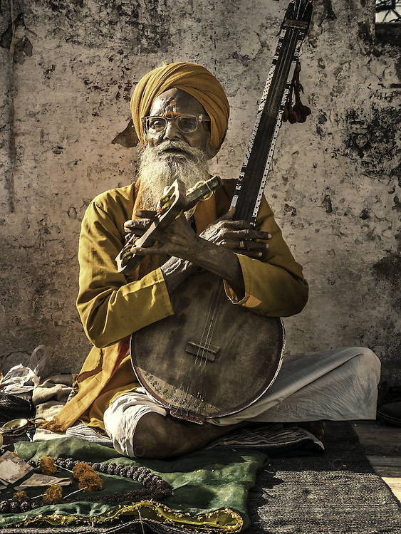 Senior musician playing music and singing at the entrance of the Jagdish temple in Udaipur India.