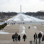 Tourists climb the steps of the Lincoln Memorial, with the Reflecting Pool in the background drained for the winter.