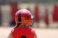 young girl at third base in a softball game with red uniform and red helmet