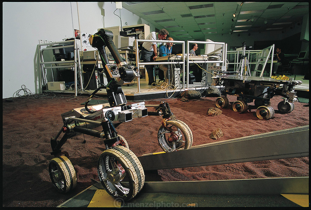 Under the control of NASA engineers (from left) Eric Baumgartner, Hrand Aghazarian, and Terry Huntsberger, the Mars Rover robot slowly carries its small payload of rock debris and dirt up the ramp to its mother ship. The rover was scheduled to be sent to Mars on two missions, in 2003 and 2005. Jet Propulsion Laboratory in Pasadena, California. From the book Robo sapiens: Evolution of a New Species, page 126.