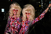 New York, NY - 31 October 2019. the annual Greenwich Village Halloween Parade along Manhattan's 6th Avenue. A couple dressed as two women with big hair from the 60s.