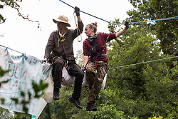 Denham, UK. 24 July, 2020. Larch (l) and Swan (r), environmental activists from HS2 Rebellion, sit on a line above the shallow river Colne attached to an ancient alder tree to try to protect it from destruction in connection with works for the HS2 high-speed rail link in Denham Country Park. Swan remained on the line for almost fourteen hours before her safety line was cut during a policing operation involving the Metropolitan Police, Thames Valley Police, City of London Police and Hampshire Police.