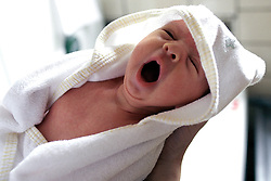 BRUSSELS, BELGIUM - JUNE 31, 2001 - A new born baby yawns after being bathed and swaddled. (PHOTO © JOCK FISTICK