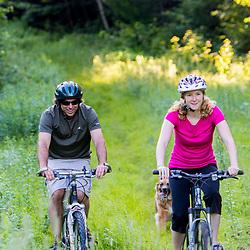 A couple rides their mountain bikes on the edge of a forest in Duxbury, Vermont.