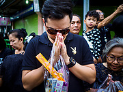 13 OCTOBER - BANGKOK, THAILAND:  A man prays on the first anniversary of the death of Bhumibol Adulyadej, the Late King of Thailand. About 199 monks from 14 Buddhist temples in Bangkok participated in the mass merit making at Siriraj Hospital to mark the anniversary of the revered King's death. He will be cremated on 26 October 2017.  PHOTO BY JACK KURTZ