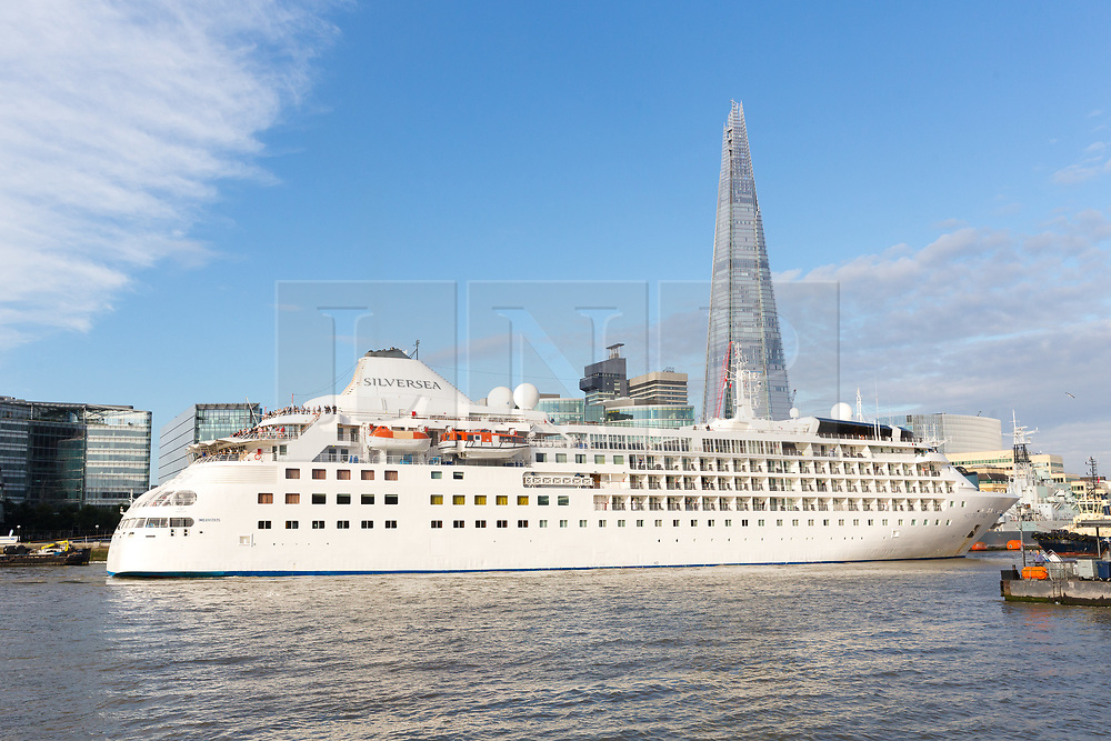 © Licensed to London News Pictures. 01/08/2017. LONDON, UK.  Silver Wind, a huge 514 feet long, 17,400 ton cruise liner leaves London passing the Shard before travelling under Tower Bridge this morning after a brief visit, towed backwards by two tugs. Silver Wind carries just 296 passengers and its owner, Silversea claim that the ship has amongst the highest space-to-guest ratios in the cruise ship industry, with the largest suites measuring 1,314 square feet. Tickets cost thousands of pounds, but all guest expenses, even champagne are included in the price. Environmentalists claim thepollutioncreated by giantcruise ships outweigh their economic benefits. The Port of London Authority (PLA) are conducting a work programme during 2017 to monitor air quality and pollution caused by river traffic on the River Thames.  Photo credit: Vickie Flores/LNP