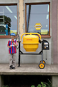Polish boy age 8 standing beside yellow cement mixer in front of a hardware store. Rzeczyca Central Poland