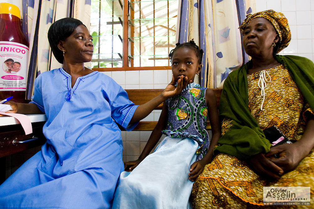 Nurse Cécile Aka Ahoua (left) examines seven-year-old daughter Aishata Konante who waits with her mother Ahoua Konante at the NDA health center in Dimbokro, Cote d'Ivoire on Friday June 19, 2009. Aishata suffers from fever, cough and muscle pains.