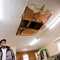 010613       Cable Hoover<br /> <br /> Pastor Shiame Okunor looks over the ceiling damage in the kitchen of the Howard Chapel in Gallup Sunday.