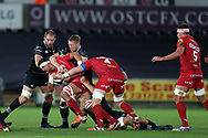 Aaron Shingler of the Scarlets is tackled by Alun Wyn Jones (l) and Bradley Davies of the Ospreys. Guinness Pro14 rugby match, Ospreys v Scarlets at the Liberty Stadium in Swansea, South Wales on Saturday 7th October 2017.<br /> pic by Andrew Orchard, Andrew Orchard sports photography.