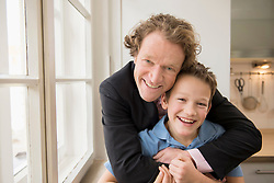Portrait of father in suit hugging son