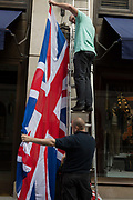 In the week of US President Donald Trumps state visit to the UK, employees check on which way up the British Union Jack flag should hang outside the American clothing retailers Bond Street address, on 5th June 2019, in London, England.