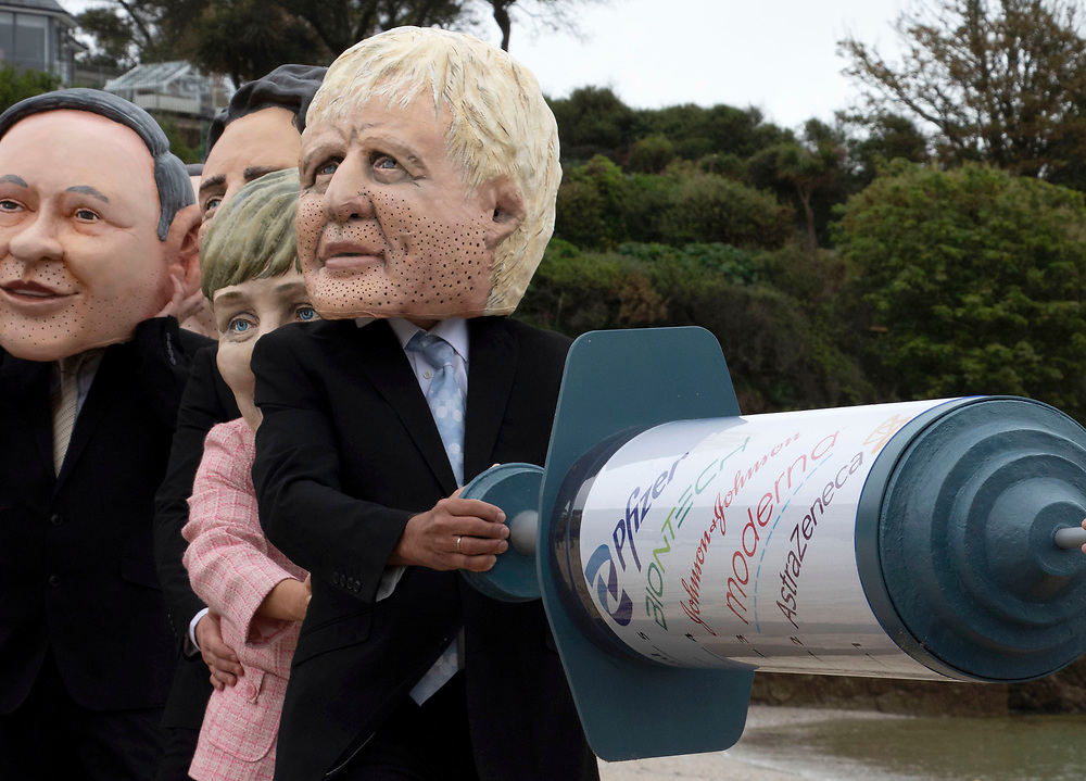 A caricature of Boris Johnson holds a giant vaccine needle, along with other members of the G7, as part of the People's Vaccine movement. Swanpool beach, Cornwall. 11th JUne 2021. Anna Hatfield/Pathos