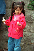 Girl with lollipops age 6 at Cinco de Mayo festival.  St Paul Minnesota USA