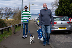 Edinburgh, Scotland, UK. 31 March, 2020. Police patrol public parks and walking areas to enforce the coronavirus lockdown regulations about being outdoor. Men wearing face masks walk dog at Gypsy Brae park. Iain Masterton/Alamy Live News