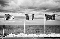 Black and white view of USA, French, and Europe Flags found along the Promenade des Anglais, Nice, France.