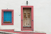 An old wooden doorway with pink detail and blue shutters on a historic house in San Miguel de Allende, Mexico. San Miguel de Allende has more than 2,000 old wooden colonial doors dating from the 1800's making the city unique in Mexico.