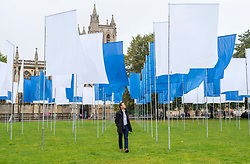 """© Licensed to London News Pictures; 01/10/2021; Bristol, UK. Artist LUKE JERRAM views his work """"In Memoriam"""" installed on College Green in front of Bristol Cathedral. The work, made up of over 100 flags which have been made from NHS hospital bed sheets, has been created in memorial to the losses experienced during the COVID-19 pandemic, and is open to the public from 1st – 17th October. Jerram has toured this installation throughout the UK and Europe but now brings it to his hometown of Bristol. Photo credit: Simon Chapman/LNP."""