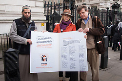 London, February 14th 2015. Dozens of orange boiler-suit clad protesters march from Parliament Square to Downing Street in protest against the ongoing detention in Guantanamo Bay of British subject Shaker Amer, who has been held without charge for 13 years. PICTURED: Shaykh Suluman Gani, left, and petition organiser Joanne MacInnes are joined by Peter Oborne outside Downing street ahead of delivering a petition to Number 10.