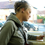 Girl looking out of the window of Lilia's cafe, Parson Cross, Sheffield, South Yorkshire, UK