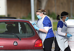 EDITORS NOTE: NUMBER PLATE PIXELATED BY PA PICTURE DESK Medical staff taking samples at 10.10am at an NHS drive through coronavirus disease (COVID-19) testing facility at Chessington World of Adventures, in Greater London, as the UK continues in lockdown to help curb the spread of the coronavirus.