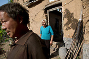 58 year old Qiao Jinchao and his wife Tan Minquan stand in front of their house in Maijieping Village, near Dengfeng, Henan Province, China on 23 October,  2013. Once the home to some 200 people, the village of Maijieping has seen its numbers dwindled to only four permanent  residents as most have moved to more convenient locations with access to jobs, schools, and hospitals.