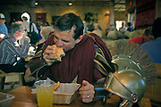 """Orlando, Florida, USA, February 2001..The Holy Land Experience is theme park with a twist. Described as a """"living Biblical museum"""", it is founded by Zion's Hope, a Baptist sect of converted Jews. A member dressed as a Roman centurian bites into a hamburger in the Oasis cafe..."""