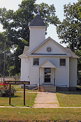23 August 2013:   A small wood framed white church in Bellflower Illinois currently under repair of the entry is home to the St. John's Catholic Church congregation.
