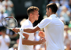 Novak Djokovic consoles Adam Pavlasek following his victory on day four of the Wimbledon Championships at The All England Lawn Tennis and Croquet Club, Wimbledon.
