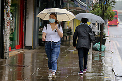 © Licensed to London News Pictures. 14/09/2021. London, UK. A woman wearing a face covering shelters under an umbrella during rainfall in north London. A yellow weather warning for heavy rain is in place in London and parts of South East England. Photo credit: Dinendra Haria/LNP
