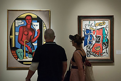 """© Licensed to London News Pictures. 29/06/2017. London, UK.  Members of the public view (L to R) """"Les Masques"""", 1928, by Jean Metzinger and """"Le Tapis Rouge Dans Le Paysage"""", 1952, by Fernand Léger during a visit to Masterpiece London, a leading art fair held in the grounds of the Royal Hospital Chelsea.  The fair brings together 150 international exhibitors presenting works from antiquity to the present day and runs 29 June to 5 July 2017.  Photo credit : Stephen Chung/LNP"""