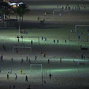 Locals play football at night under floodlight on Copacabana beach, Rio de Janeiro, Brazil. 21st July 2010. Photo Tim Clayton..
