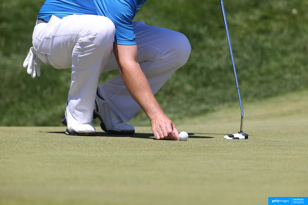 A golfer places his ball before putting. Photo Tim Clayton