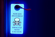 """A glowing """"Already Disturbed"""" sign hangs from a door knob.Black light"""