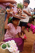 Laden with flowers and doughnut at a village market.<br /> Tenasserim region, Burma 2000. Face covered with Thanaka, a yellowish cosmetic paste made from ground bark which is commonly applied to the face in Burma.