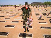 26 MAY 2012 - PHOENIX, AZ: Pfc. KEVYNN BRAND, a member of the Firebirds Young Marines, from Phoenix, AZ, salutes after placing an American flag on a veteran's grave at the National Memorial Cemetery in Phoenix, AZ, Saturday. Hundreds of Boy and Girl Scouts along with the Young Marines, a Scout like organization, place American flags on veterans' graves in the National Memorial Cemetery in Phoenix every year on the Saturday before Memorial Day.       PHOTO BY JACK KURTZ