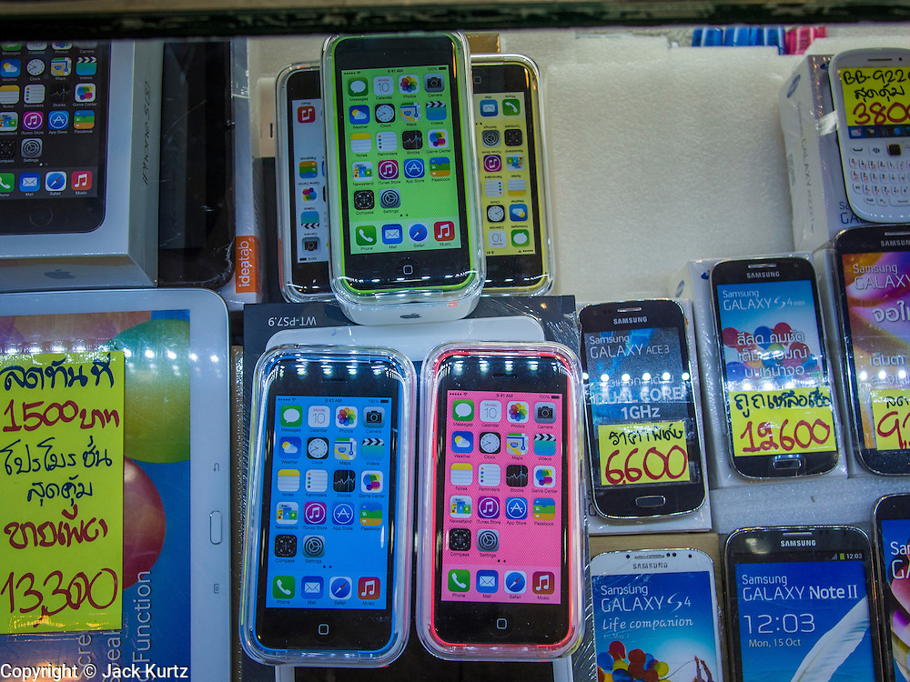 21 SEPTEMBER 2013 - BANGKOK, THAILAND: Boxed iPhone 5c models in a display case in an electronics shop in MBK in Bangkok. Customers around the world lined up Friday to pick up Apple's new flagship iPhone 5s and its lower cost, more colorful brother, the iPhone 5c. The phones went on sale in the US and select countries beyond the US on Friday. The iPhone 5s and iPhone 5c will not be officially released in Thailand until late 2013 but the phones are available through the unofficial grey market in MBK, a huge shopping complex in Bangkok with dozens of small electronics shops. Early purchasers in Thailand pay a premium for the new iPhones, the top of the line iPhone 5s with 64 gigabytes of memory is about 38,500Baht, more than $1,200 (US).     PHOTO BY JACK KURTZ