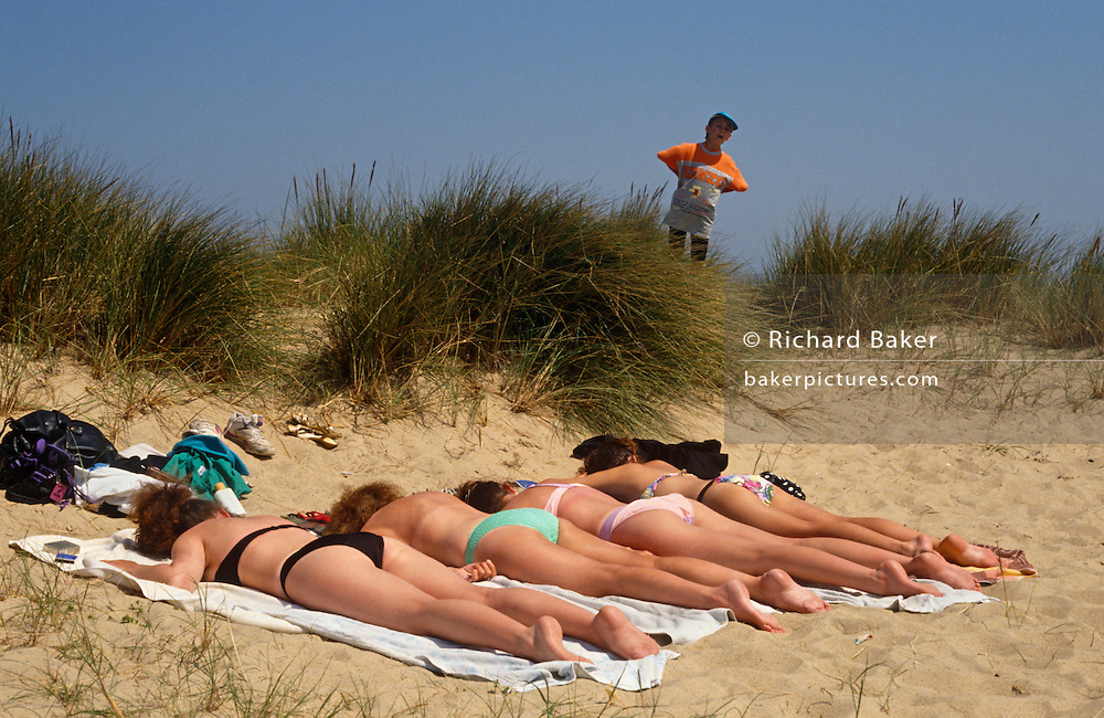 A pre-pubescent voyeur peers over a clump of vegetation to spy on four beautiful women lying face-down in a sandy dune near the seaside resort of Great Yarmouth, Norfolk.