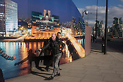 A kind stranger retrieves a hat belonging to another pedestrian by a construction hoarding, a night time panorama of the Thames south bank, featuring the HQ of the intelligence service (MI6) across the river in Vauxhall.