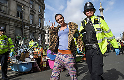 © Licensed to London News Pictures. 10/10/2019. London, UK. An Extinction Rebellion activist gestures a V sign while being arrested for refusing to move from the roads around Trafalgar Square in Westminster, central London where they have been demonstrating for a fourth day running. The climate change group have blockaded the Westminster area, demanding that the government takes immediate and decisive action on climate change. Photo credit: Ben Cawthra/LNP