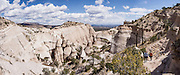 "Hoodoos panorama. See fantastic hoodoos and a great slot canyon in Kasha-Katuwe Tent Rocks National Monument, in New Mexico, USA. Hike the easy Cave Loop Trail plus Slot Canyon Trail side trip (3 miles round trip), 40 miles southwest of Santa Fe, on the Pajarito Plateau. Distinctive cone-shaped caprocks protect soft pumice and tuff beneath. Geologically, the Tent Rocks are made of Peralta Tuff, formed from volcanic ash, pumice, and pyroclastic debris deposited over 1000 feet thick from the Jemez Volcanic Field, 7 million years ago. Kasha-Katuwe means ""white cliffs"" in the Pueblo language Keresan. This panorama was stitched from 8 overlapping photos."